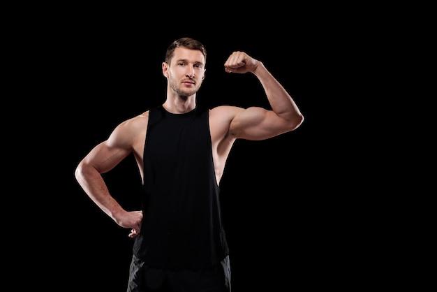 Jonge sterke atleet in sportkleding die een hand op de taille houdt terwijl hij zijn kracht in isolatie toont
