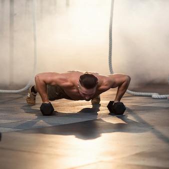 Jonge sterke man doet pushups met halters tijdens de training in de sportschool.