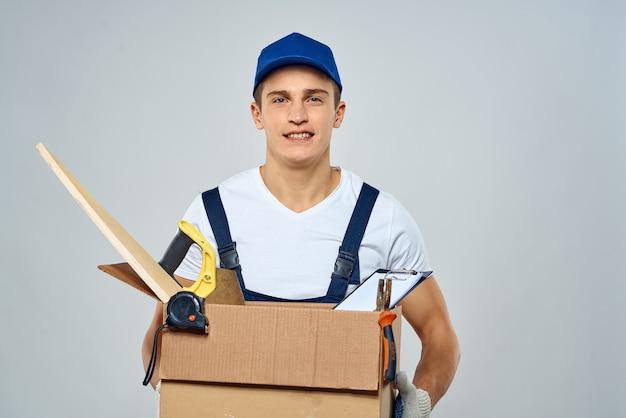 Jonge sterke man in overall levert doos