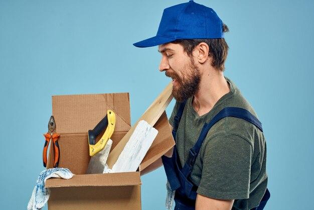 Jonge sterke man in overall levert pakketten, dozen, goederen, koerier