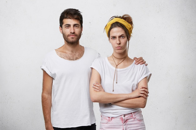 Jonge sterke man met baard en trendy kapsel omarmen zijn vriendin terwijl hij tegen een witte muur staat.