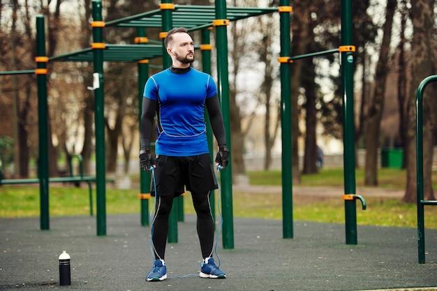 Jonge sterke man met een touw op een sportveld in de zomer