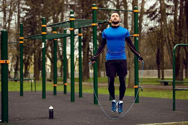Jonge sterke man springen met touw op sportveld in de straat in de zomer