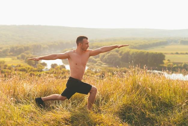 Jonge sterke man strekt zich buiten uit in de natuur.