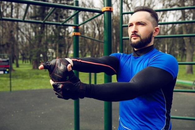 Jonge sterke man strekt zich uit zijn spieren voor de training