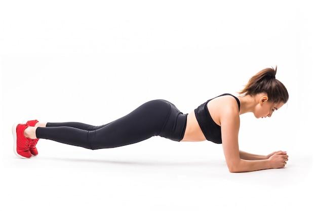Jonge sterke sportvrouw beoefenen van yoga zonder mat.
