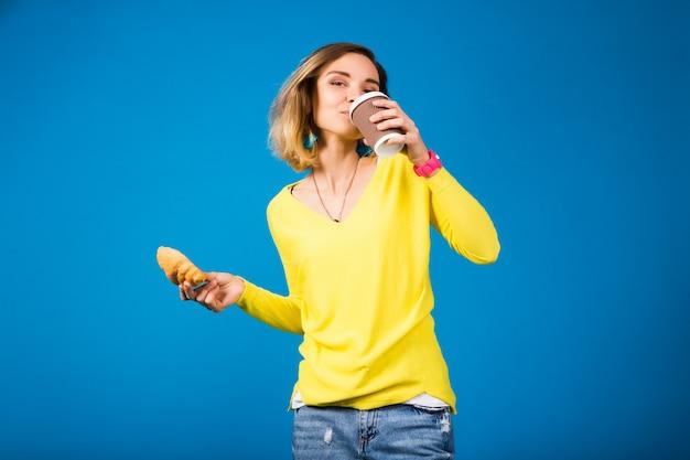 Jonge stijlvolle aantrekkelijke vrouw in gele blouse op blauw