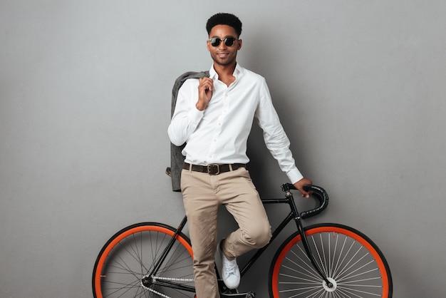 Jonge stijlvolle afro-amerikaanse man permanent en leunend op de fiets