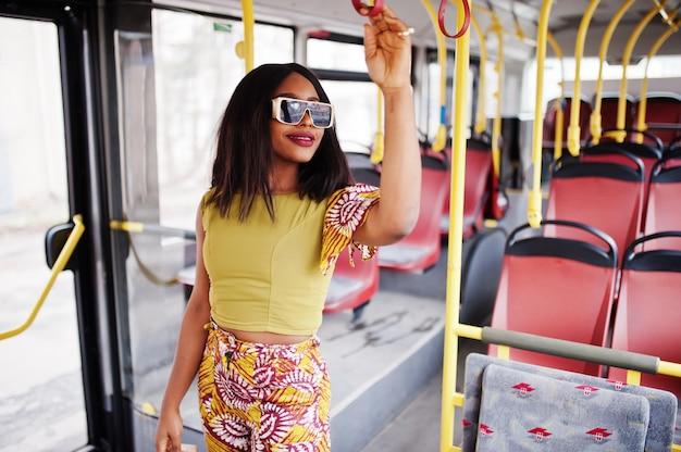 Jonge stijlvolle afro-amerikaanse vrouw in moderne zonnebril rijden op een bus.