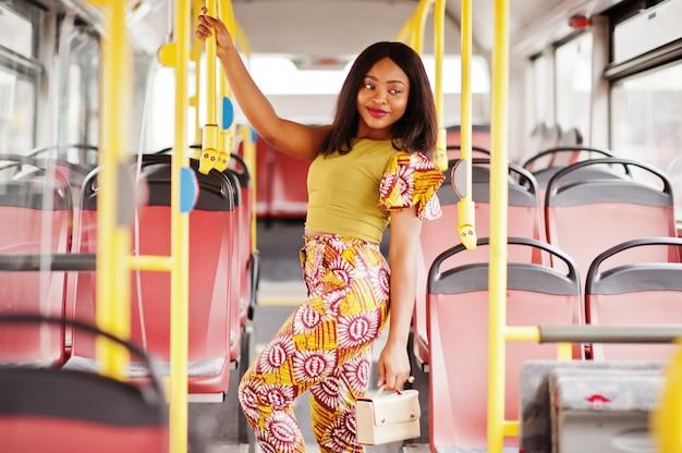 Jonge stijlvolle afro-amerikaanse vrouw rijden op een bus.