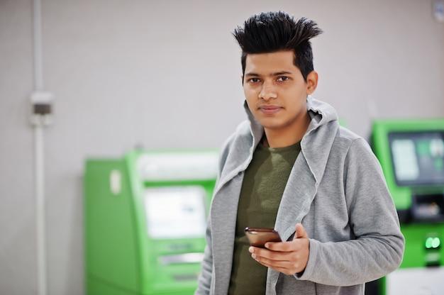 Jonge stijlvolle aziatische man met mobiele telefoon tegen rij van groene atm