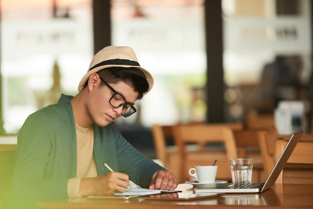 Jonge stijlvolle aziatische man zit in café met laptop en schrijven in notitieblok