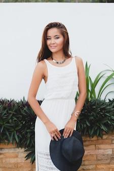 Jonge stijlvolle aziatische vrouw in witte boho-jurk, vintage stijl, natuurlijk, glimlachend, gelukkig, tropische vakantie, hotel, honingmaan