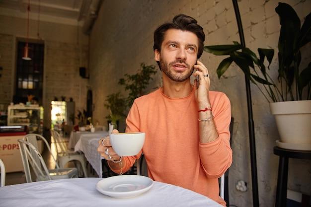 Jonge stijlvolle bebaarde man die zich voordeed op koffiehuis, praten aan de telefoon met kopje thee in de hand en praten over de telefoon, perzik kleur trui dragen