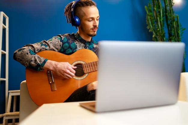 Jonge stijlvolle blanke man die gitaarles online thuis met behulp van zijn laptop