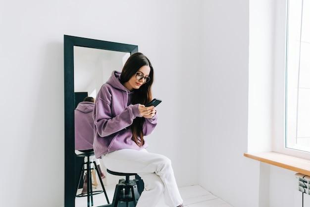 Jonge stijlvolle blanke vrouw met behulp van mobiele telefoon in de buurt van grote spiegel, zittend op een zwarte stoel in witte kamer in de buurt van raam.