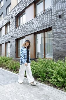Jonge stijlvolle brunette vrouw model loopt op de achtergrond van de straat van de stad poseren in nieuwe mooie kleding