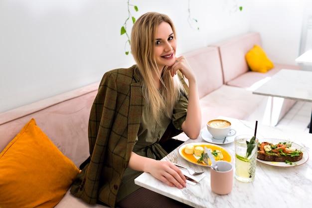 Jonge stijlvolle elegante vrouw genieten van haar smakelijk ontbijt in stijlvolle café hipster, 's ochtends tijd, elegante outfit.