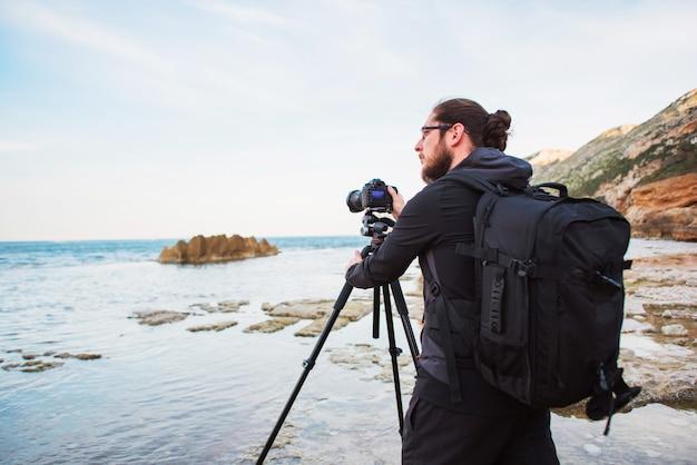 Jonge stijlvolle fotograaf foto's van zee maken met de camera op een statief