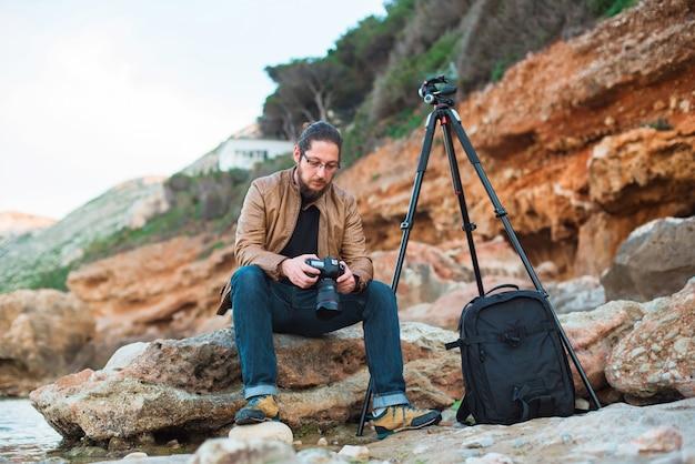 Jonge stijlvolle fotograaf zittend op een rots en kijken naar foto's die hij op zijn camera heeft gemaakt