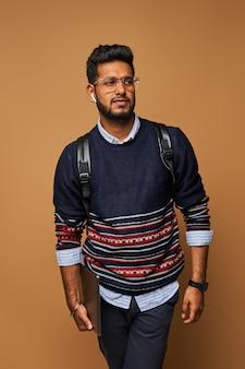 Jonge stijlvolle handome indiase man met rugzak en laptop in glazen op de muur.