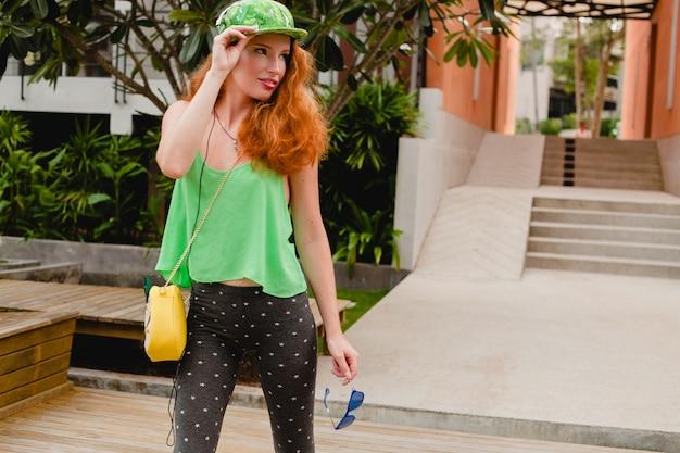 Jonge stijlvolle hipster gember vrouw, dansende luistermuziek, koptelefoon, groene pet, legging, zonnebril, plezier hebben, trendy modieuze outfit, ontspannen, tiener-, trendaccessoires