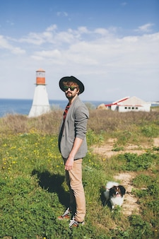 Jonge stijlvolle hipster man in hoed wandelen met hond op platteland