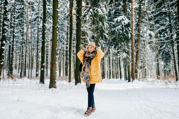 Jonge stijlvolle hipster meisje in gele jas met een warme sjaal poseren in het sneeuwbos