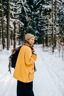 Jonge stijlvolle hipster meisje in gele jas met een warme sjaal wandelen in het sneeuwwoud