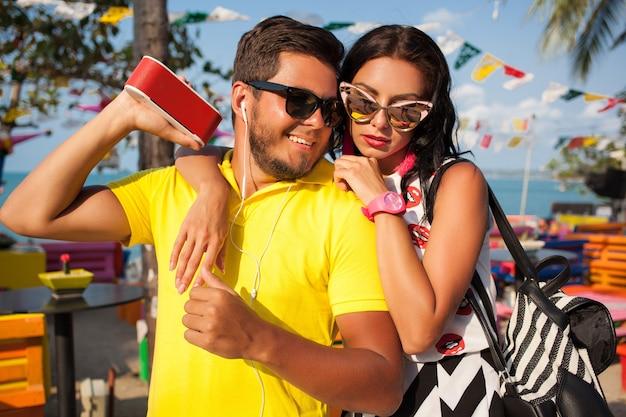 Jonge stijlvolle hipster mooie paar op zomervakantie in thailand, flirterige mode trend outfit, zonnebril, tropische romantiek, glimlachen, gelukkig, luisteren muziek, feeststemming, strandcafé