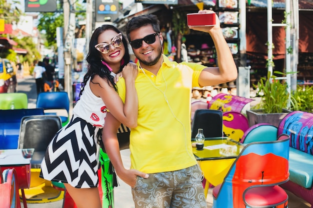 Jonge stijlvolle hipster mooie paar zittend op kleurrijk café, flirterige, mode-outfit, trendy outfit, zonnebril, tropische vakantie, vakantie romantiek, honingmaan, glimlachen, gelukkig, muziek luisteren
