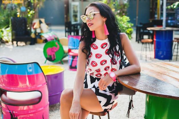 Jonge stijlvolle hipster mooie vrouw zit op kleurrijke café, flirterige, mode-outfit, trendy outfit, zonnebril, tropische vakantie,