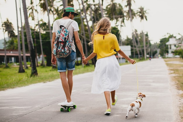 Jonge stijlvolle hipster paar verliefd op vakantie met hond en skateboard, plezier