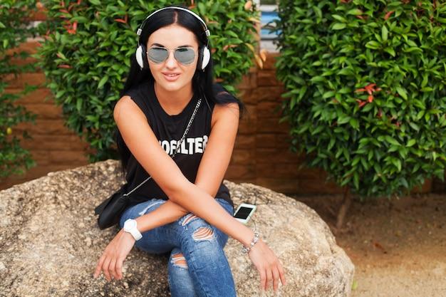 Jonge stijlvolle hipster vrouw in zwart t-shirt, spijkerbroek, luisteren naar muziek op de koptelefoon, plezier maken, poseren, grappig, glimlachen