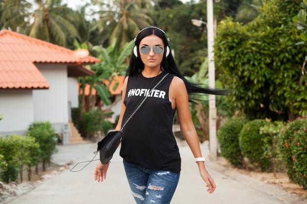 Jonge stijlvolle hipster vrouw in zwart t-shirt, spijkerbroek, luisteren naar muziek op koptelefoon, plezier, wandelen in de straat, zomervakantie, genieten van