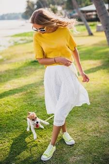 Jonge stijlvolle hipster vrouw met wandelen spelen hond puppy jack russell, tropisch park, glimlachen en plezier hebben, vakantie, zonnebril, pet, geel shirt, strandzand