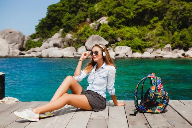 Jonge stijlvolle hipster vrouw reist de wereld rond, zittend op de pier, vlieger zonnebril, koptelefoon, luisteren naar muziek, vakantie, rugzak, denim hemd, gelukkig, tropische eilandlagune