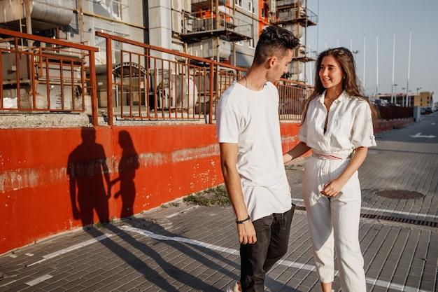 Jonge stijlvolle jongen en meisje staan in de straat op de achtergrond van stedelijk gebouw in de warme dag.