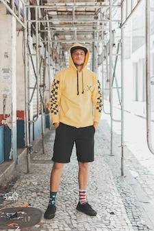 Jonge stijlvolle jongen in de straten onder steigers