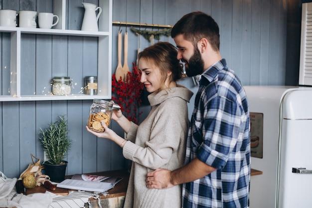 Jonge stijlvolle kaukasische paar koken, knuffelen in moderne gezellige keuken. geluk, vrijheid, familieconcept