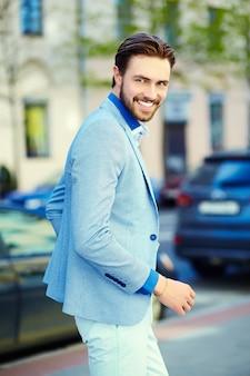 Jonge stijlvolle knappe man in pak in de straat