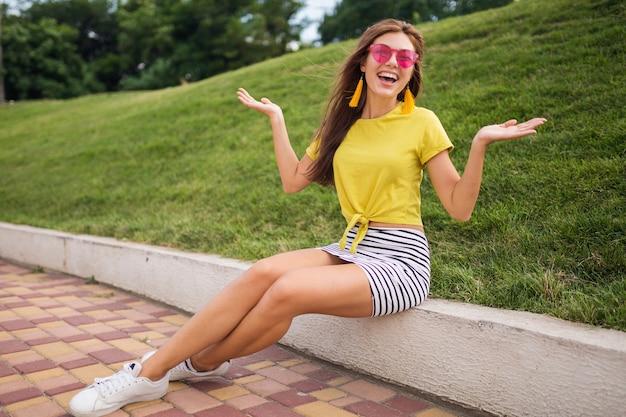 Jonge stijlvolle lachende vrouw met plezier in het stadspark, positief, emotioneel, gele top, gestreepte minirok, roze zonnebril, witte sneakers, zomerstijl modetrend, gelukkig, hand in hand omhoog