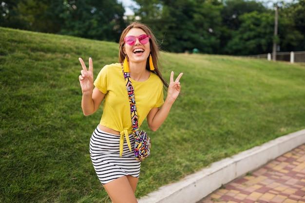 Jonge stijlvolle lachende vrouw met plezier in stadspark, lachende vrolijke stemming, positief, emotioneel, gele top, gestreepte minirok, handtas, roze zonnebril, zomerstijl modetrend dragen