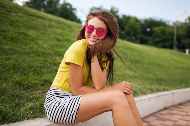 Jonge stijlvolle lachende vrouw plezier in stadspark, vrolijke stemming glimlachen, gele top, gestreepte minirok, roze zonnebril, zomer stijl modetrend dragen