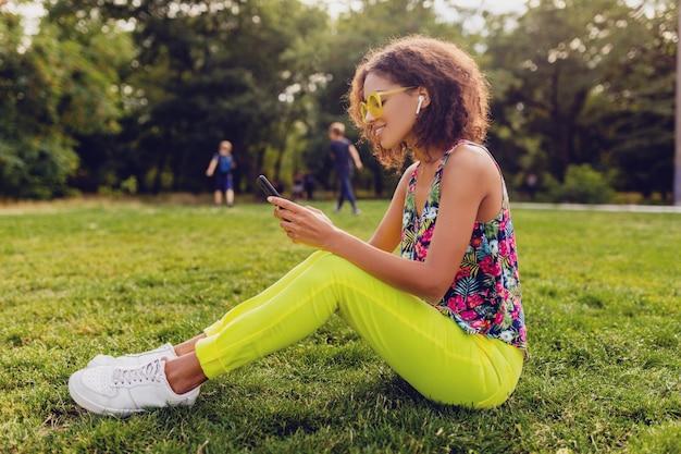 Jonge stijlvolle lachende zwarte vrouw met behulp van smartphone luisteren naar muziek op draadloze oortelefoons met plezier in park, zomer mode kleurrijke stijl
