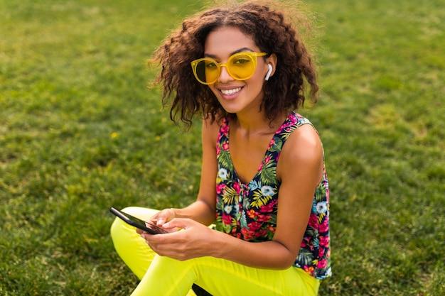 Jonge stijlvolle lachende zwarte vrouw met behulp van smartphone luisteren naar muziek op draadloze oortelefoons met plezier in park