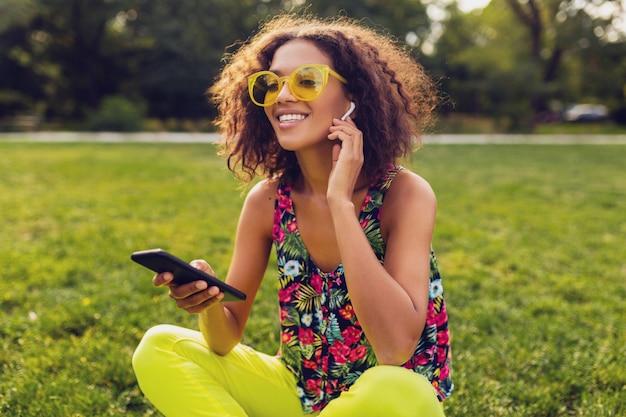Jonge stijlvolle lachende zwarte vrouw met smartphone luisteren naar muziek op draadloze oortelefoons met plezier in park, zomer mode kleurrijke stijl, zittend op gras, gele zonnebril