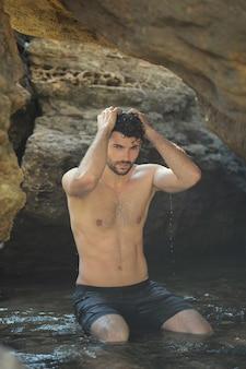 Jonge stijlvolle man buiten portret in de buurt van de zee en de rotsen, topless