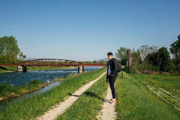 Jonge stijlvolle man die op weg in de buurt van de rivier met de rugzak