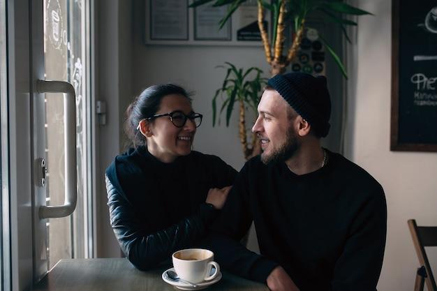 Jonge stijlvolle man en vrouw poseren binnenshuis